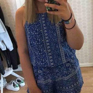 En blå mönstrad jumpsuit, riktigt fin men tyvärr billigt för liten. Öppen i ryggen. Bara att fråga om du vill ha bild hur den ser ut på !