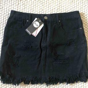 Svart jeanskjol från Boohoo med slitningar. Köpt förra sommaren men aldrig använt, lappar finns kvar.