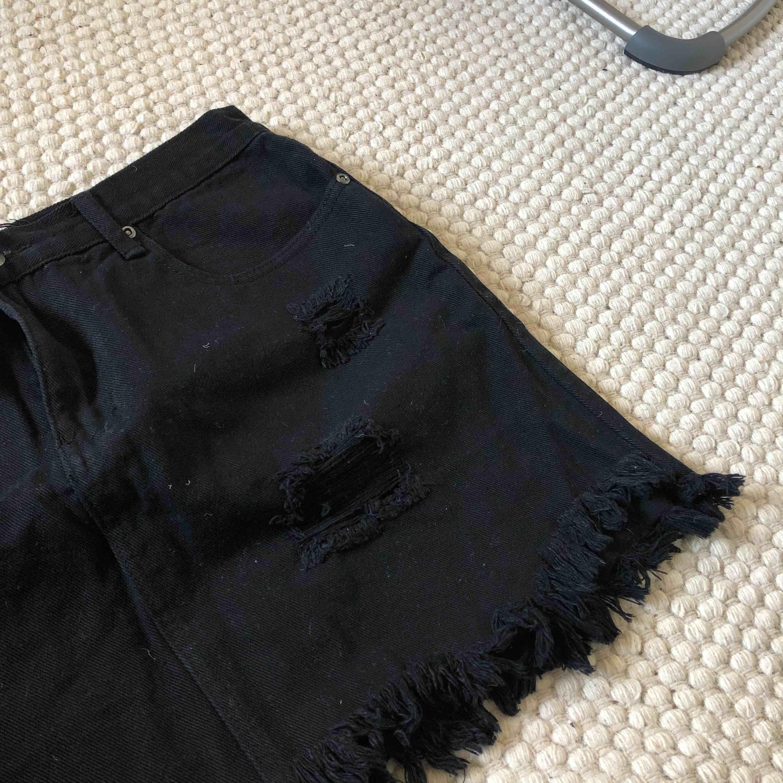 Svart jeanskjol från Boohoo med slitningar. Köpt förra sommaren men aldrig använt, lappar finns kvar. . Kjolar.
