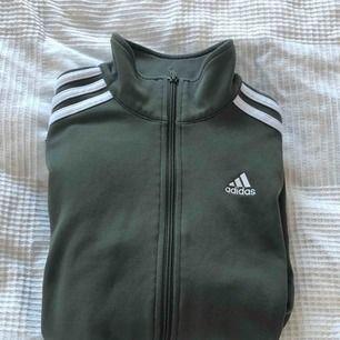 Olivgrön Adidas jacka.   Säljer eftersom den ej kommer till användning.   Kan mötas i Bålsta eller frakta. Tar endast emot Swish.  Kunden står för den eventuella frakten.