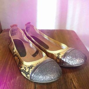 Vikbara ballerinaskor med mjuk sula. Signatur för Tamaris är att de producerar bekväma skor. Ybertrendigt med ormskinns imitation! Snygga på kontoret, flygresan eller sommaren.