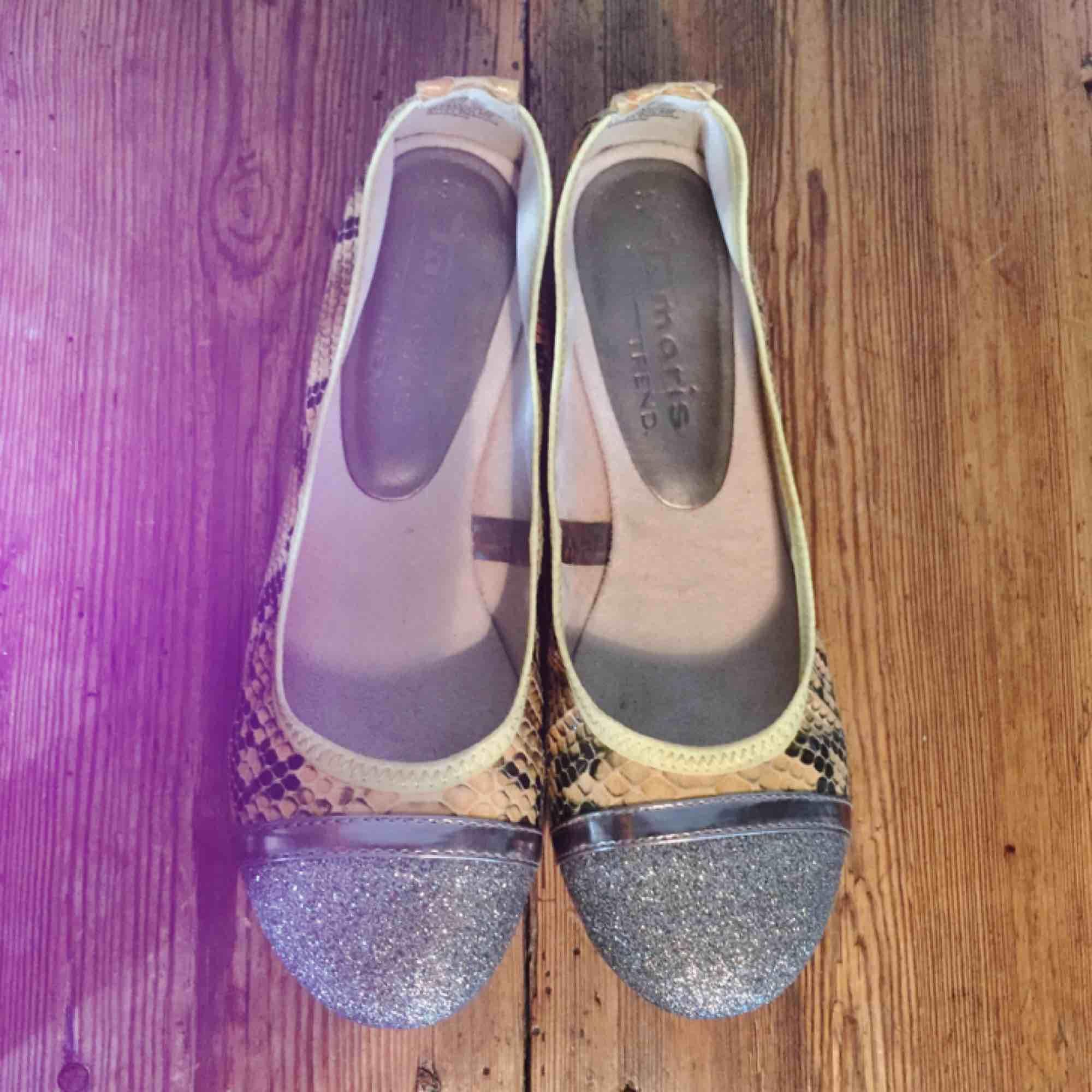 Vikbara ballerinaskor med mjuk sula. Signatur för Tamaris är att de producerar bekväma skor. Ybertrendigt med ormskinns imitation! Snygga på kontoret, flygresan eller sommaren. . Skor.