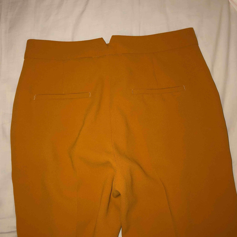 Oanvända kostymbyxor från Zara i senapsgul färg. Jeans & Byxor.