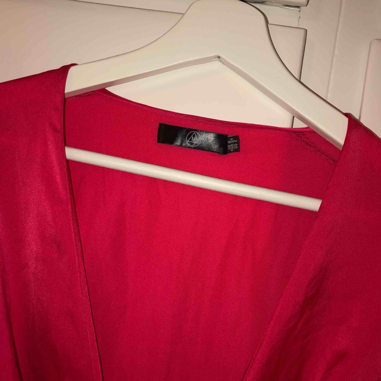 Oanvänd klänning från Nelly i röd/rosa färg. Klänningar.