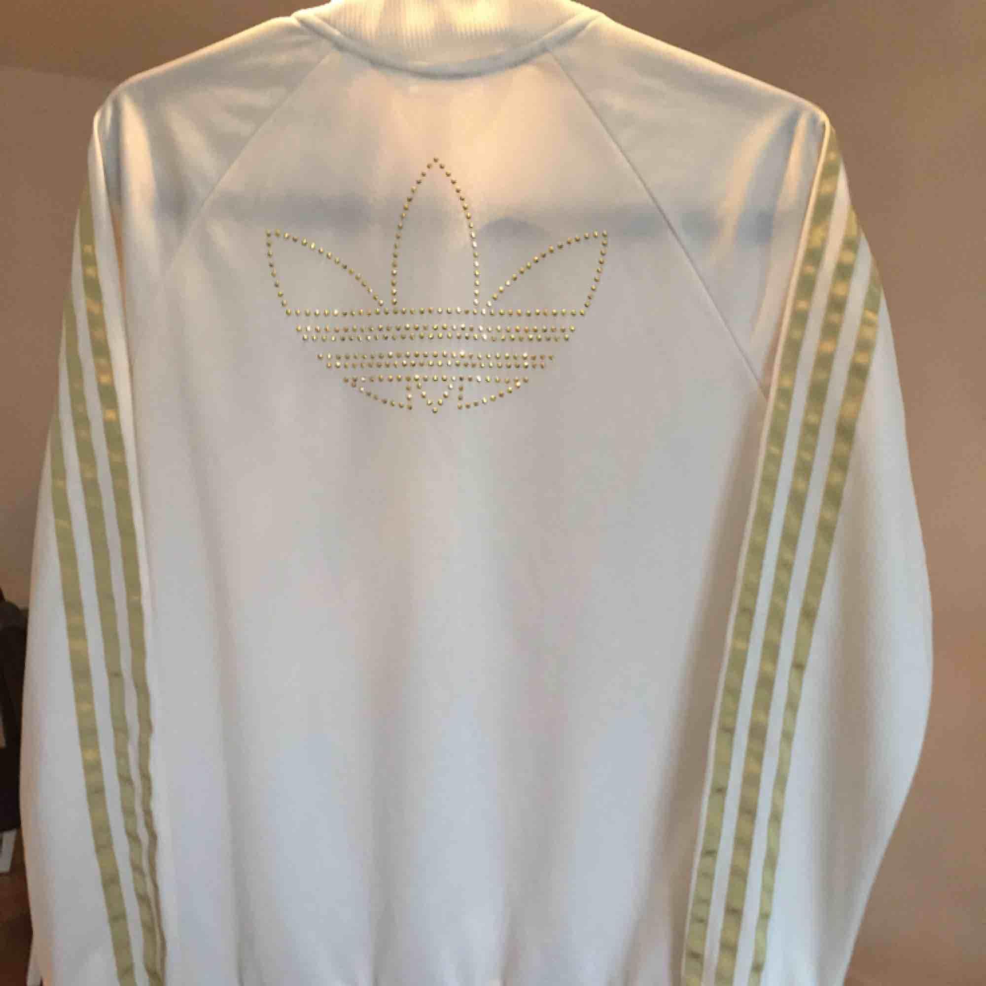 Superfin och lite ovanlig Adidas tröja Vit med detaljer i guld och är i mycket bra skick Kom med bud och kolla gärna mina andra annonser, kan samfrakta i den mån det går Går ej att swisha, men går bra med kontanter eller banköverföring. Huvtröjor & Träningströjor.