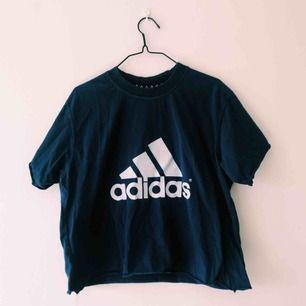 Mörkblå lite croppad T-shirt från adidas. Köpt på second hand. Den är lite oversize men sitter snyggt på mig som är en M och lång :)  Frakt tillkommer
