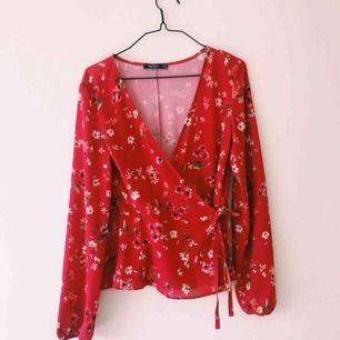 Röd omlott-blus från bershka köpt i Berlin på en second hand! Använd fåtal gånger. Frakt tillkommer :)
