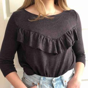 Grå/svart tröja med 3/4 armar och volang över brösten. Köpare står för frakt!😁