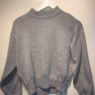 En skön, ljusgrå tröja med polo. Perfekt för kallt väder, knappt använd.