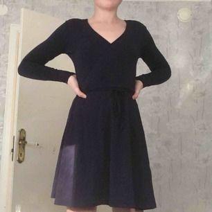 En marinblå omlott klänning. Den är långärmad och ett snöre som man kan knyta i midjan. Aldrig använd, köpt för 300kr.