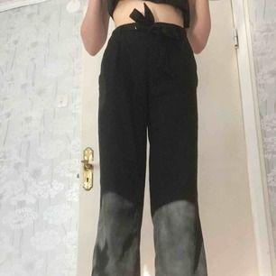 Ett par svarta, kostymliknande byxor med tygskärp i midjan. De är breda vid benen och har fickor. Köpta för 250kr.