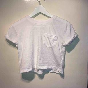 En vit magtröja med en ficka på höger sida. Köpt för 80kr.