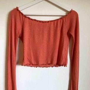 Orange offshoulder tröja.