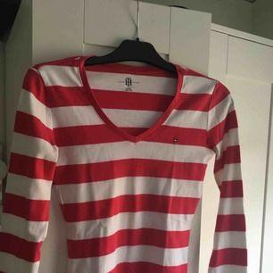 En rosa-vit randig långärmad tröja från Tommy hilfiger! i storlek XS och i bra skick !  Kontakt: 0732500530(nås på sms) Teamarkholm@gmail.com  Köparen står för frakt! 🥰