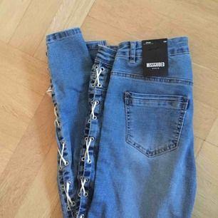 Helt oanvända jeans från Nelly med snörningar på sidan av båda benen. Stretchiga. Säljer för att de är för stora