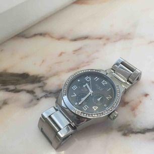 Helt oanvänd silver klocka från Regal. Har ett batteri som behöver bytas men kan fixas lätt och billigt, därav priset. Armbandet kan justeras.
