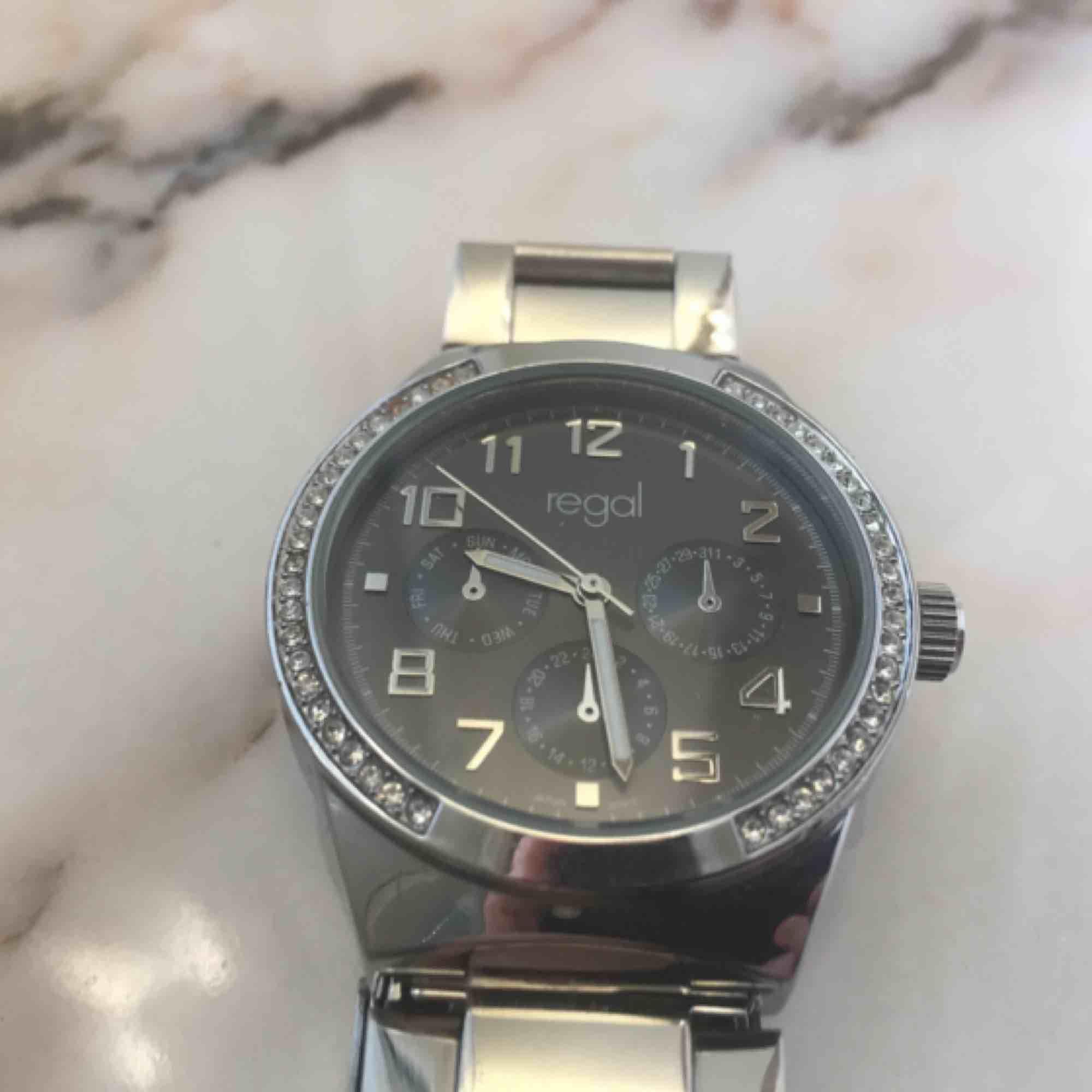Helt oanvänd silver klocka från Regal. Har ett batteri som behöver bytas men kan fixas lätt och billigt, därav priset. Armbandet kan justeras. . Accessoarer.