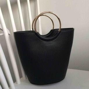 Fin svart bucket väska med guldringar. Använd endast en gång så den är i nyskick! Ca 23cm hög. Axelrem medföljer!   Hämtas i Malmö eller postar för 50kr💕