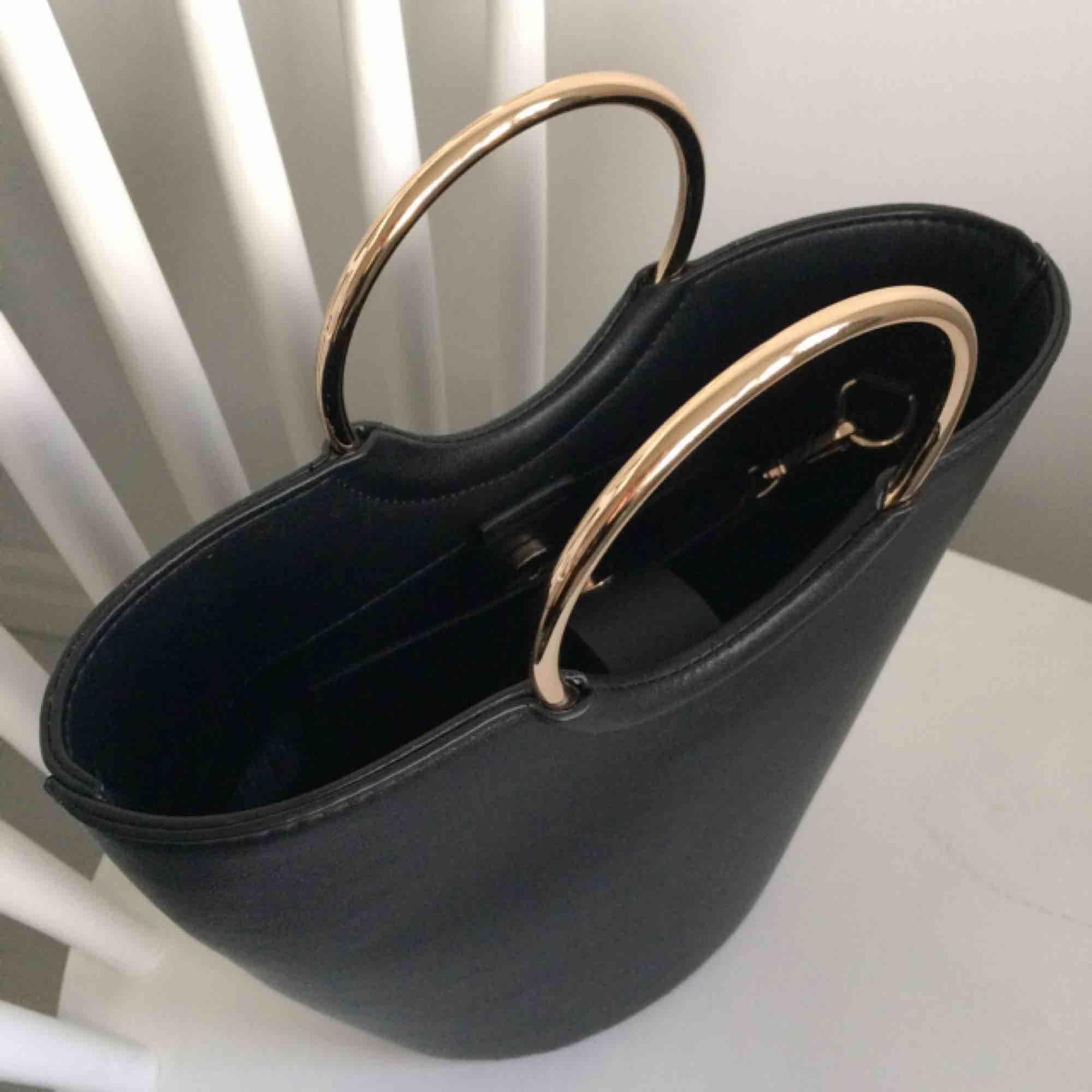 Fin svart bucket väska med guldringar. Använd endast en gång så den är i nyskick! Ca 23cm hög. Axelrem medföljer!   Hämtas i Malmö eller postar för 50kr💕. Väskor.
