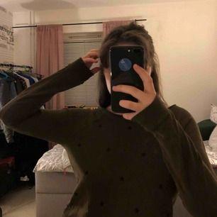 En militärgrön tjockare tröja med svarta stjärnor på, använt få gånger, säljer på grund av att den är lite för liten💕