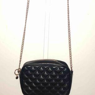 Jätte fin svart liten väska med guldiga detaljer! Man får plats mycket i den väskan telefon, plånbok och annat övrigt.