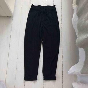 Svarta lösa högmidjade kostymbyxor från Gina tricot.  Använda 1 gång. Lösa längst ner och längst upp vid låren. Inget stretch material. Två fickor på fram sidan och två fake vid rumpan. Ett snöre som går vid midjan