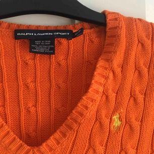 En kabelstickad tröja från Ralph lauren. Tröjan är orange med gult märke! Den är använd fåtal gånger och i bra skick! Den är i storlek XS  Kontakt: 0732500530(nås på sms) Teamarkholm@gmail.com  Köparen står för frakten 🥰🥰