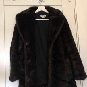 """En supersnygg kappa/jacka i mörkbrun fuskpäls. Den är från H&M i storlek EUR 34. Riktigt fin är den, """"pälsen"""" är väldigt fin och dör för färgen."""