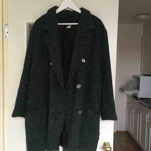 Mörkgrön kappa med lite spräckliga färger i. Jag har i vanliga fall storlek Medium.  Köpte den för 600 kr