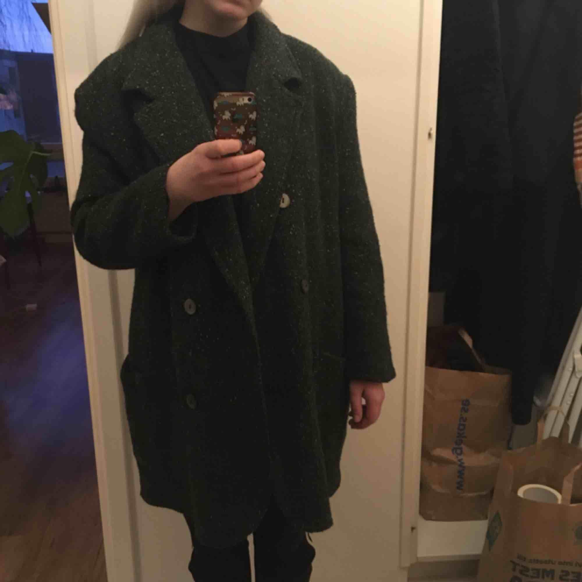 Mörkgrön kappa med lite spräckliga färger i. Jag har i vanliga fall storlek Medium.  Köpte den för 600 kr. Jackor.