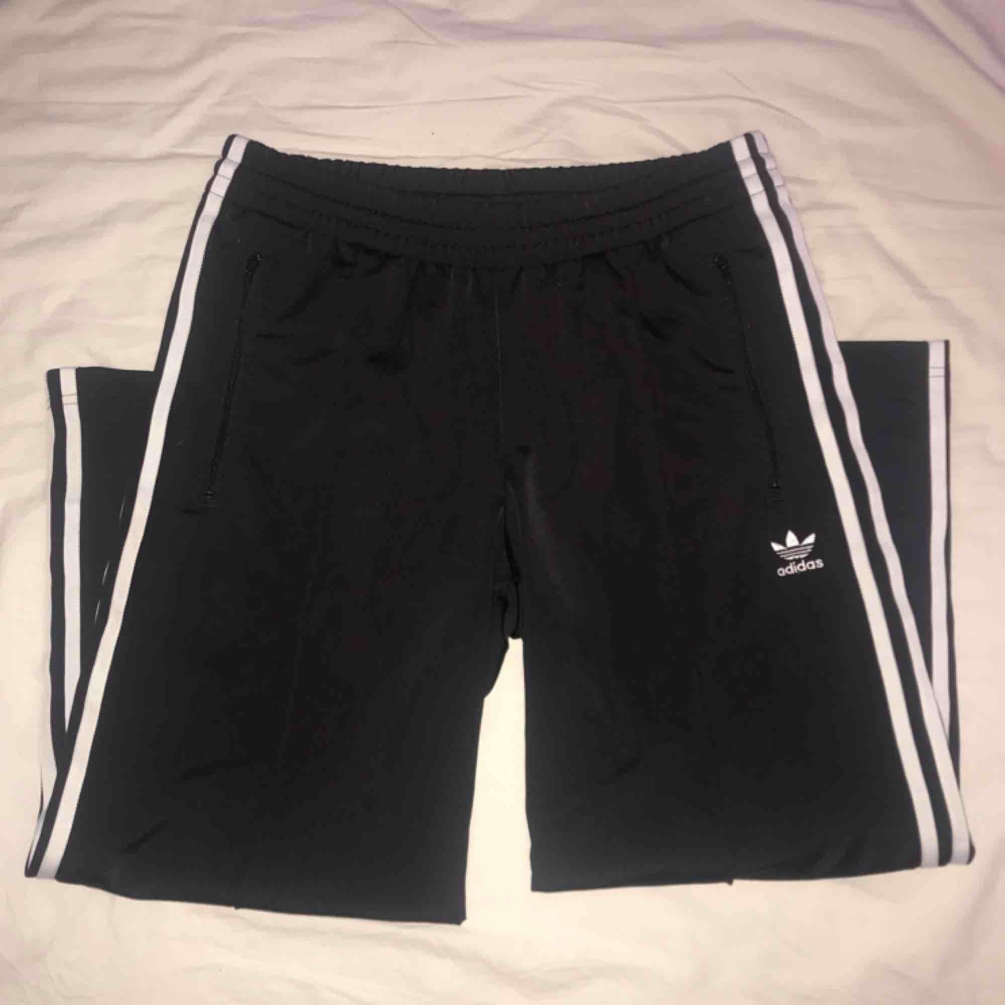 Byxor från Adidas i jättefint skick, lite glansiga i materialet och med sydda pressveck fram. Slutar precis innan fotleden. Köpare står för frakt :-). Jeans & Byxor.