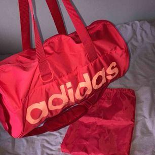 Ganska liten och smidig träningsväska från adidas. Väskan har innerfack och fack utanpå med dragkedja på vardera sida. Matchande skopåse medföljer. Har knappt använt den så den är i nyskick.