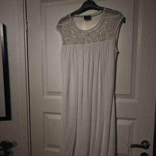 Vit klänning från VILA i stl S. Använd 1 skolavslutning. Har sminkfläckar runt halsen men går bort i tvätten eller om man skrubbar.  Rak klänning med band i midjan, pärlor/stenar upp till.  Köpt för 499kr. Postar i postnords blå kuvert, inräknat i priset.