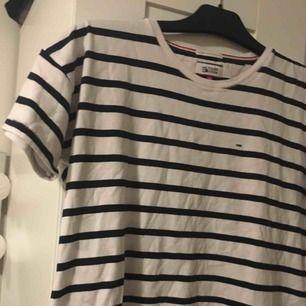 En marinblå och vit randig tshirt! T-shirten kommer från Tommy hilfiger och är i bra skick! T-shirten slutar vid höften och är pösig/ rak hela vägen. Den är i storlek XS!  Kontakt: 0732500530(nås på sms) Teamarkholm@gmail.com  Köparen står för frakten!
