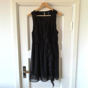 Svart klänning med detaljer i volang.