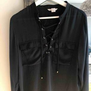 Blus/skjorta med knytning. Sidenaktikt tunt material. Ser svart ut men den är mörk mörk blå. Nyskick!