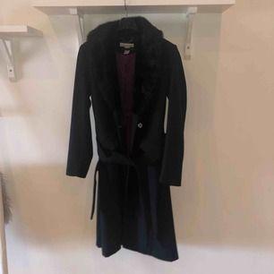 Svart kappa med fusk päls och en lila fordring, använd 1 gång och köpt i USA. Nypris 1199:-