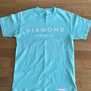 Ljusblå Diamond supply T shirt, fint skick, inga hål/brännmärken.  Köparen står för frakt.