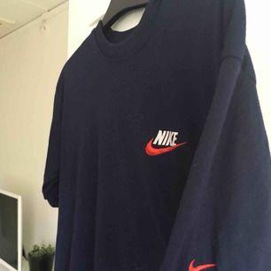 En vintage marinblå tshirt från Nike med rött och vitt märke. Storlek M och i bra skick'
