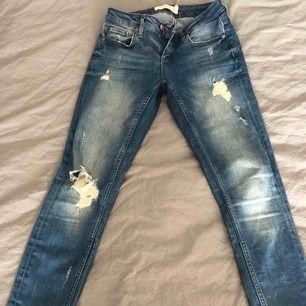 Jeans från GT. Slitningar och dragkedja vid benslut.