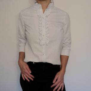 Elegant skjorta med lite krås framtill som en snygg detalj. Trekvartsärmar och smala ränder i ljusblått och vitt. I 100 % bomull och storlek 36, från H&M.