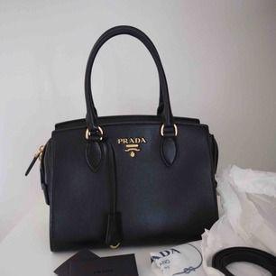 Säljer oanvänd Prada väska köpt i Italien. Colour . Nero Plast kvar på insidan Axelrem medföljer - aldrig använd. Dustbag Äkthetsbevis Kvitto Mått 26x19x13 Väskan är äkta