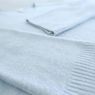 Stickad tröja från H&M med något vidare arm i rak modell. Storlek S. Svårt att få fram tröjans fina färg på bild men den är en klar ljusblå färg. Sparsamt använd.