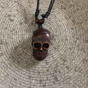 Ovanligt halsband med en dödskalle i mörkt trä på svart läderband!! Hyfsat stort hänge, passar killar lika bra som tjejer. Ej lämplig doppresent, men antagligen en de kommer minnas.