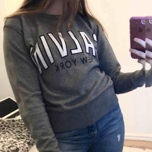 En grå crewneck / sweatshirt från Calvin Klein jeans med svart vit text. Jättebra skick - ANVÄND CIRKA 3 GÅNGER. Storlek XS. Nypris cirka 700kr