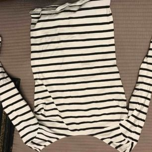 Trekvartsärmad, svart och vit randig tröja från Cubus. Urringning bak och fram, kan ha tröjan off shoulder.