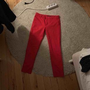 Röda kostymbyxor som sitter snyggt på rumpa och ben. Stretchiga och fina nu till våren:).