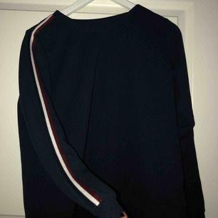 En marinblå långärmad tröja, med två streck på sidan ett rött och ett vitt. Väldigt simpel fin tröja, använd en gång ordinarie pris 199kr😁