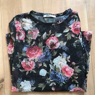 En tröja i materialet mesh, som är genomskinligt. Blomtryck på