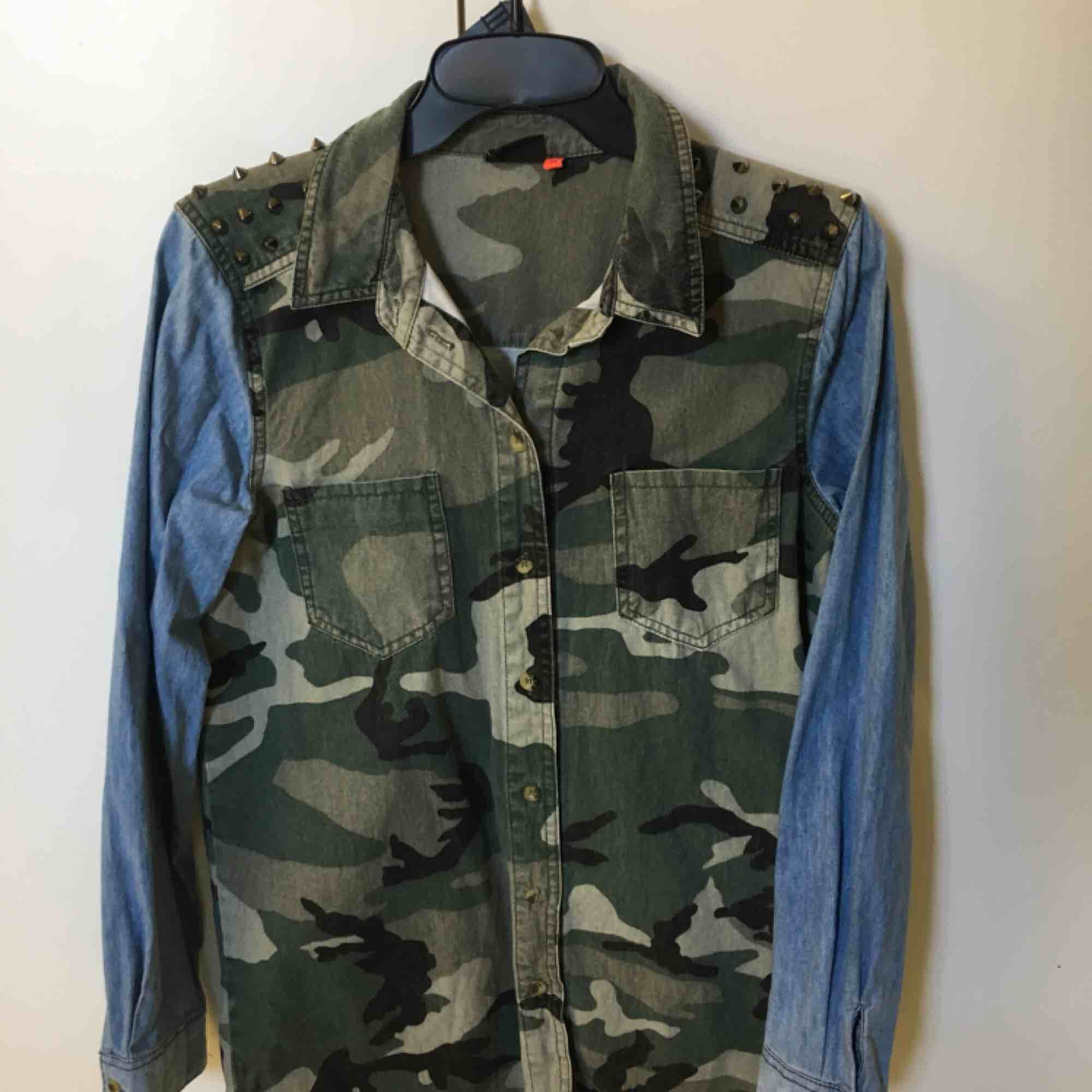 Jeans/kamouflage skjorta med nitar på axlarna. Storlek M. . Skjortor.